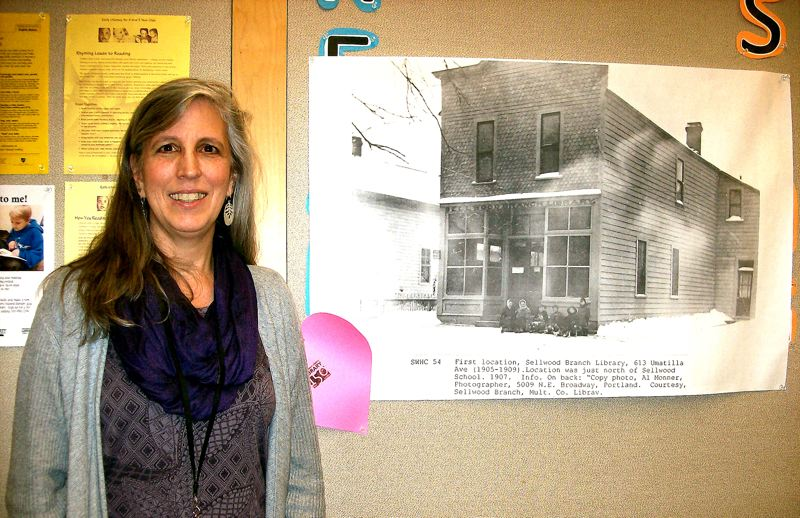 by: RITA A. LEONARD - Library Administrator Jenna Scott poses by an historic photo of the first Sellwood Branch Library, established in 1905.