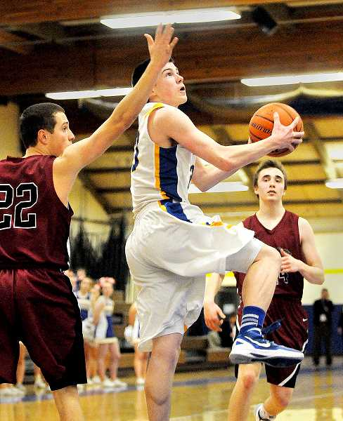by: SETH GORDON - On the rise - Jacob Pendergraph elevates to the basket during Newberg's 70-57 victory over Glencoe Feb. 25.