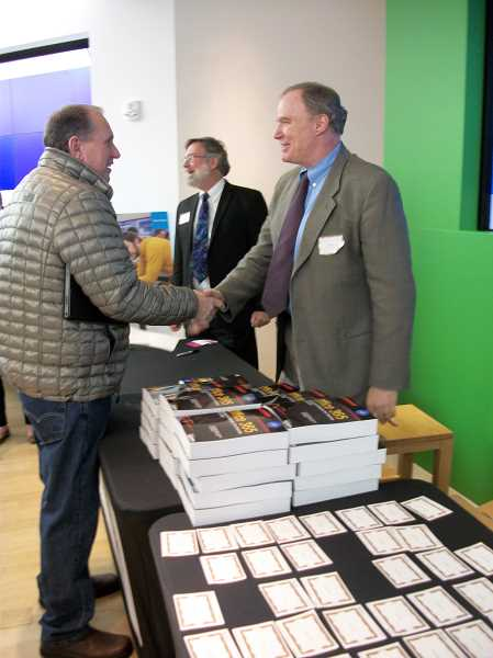 by: SUBMITTED PHOTO: DAN PEARSON - Matt Katzer shakes the hand of a book buyer at the book launch party at Microsoft in Portland. In the background is his partner and co-author, Don Crawford.