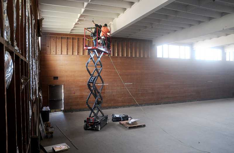 by: GARY ALLEN - Getting started - Crews began the transformation from the gymnasium at Central School into a ballroom at the Chehalem Cultural Center last week by removing ancient electrical    conduits and the wires that ran within them.