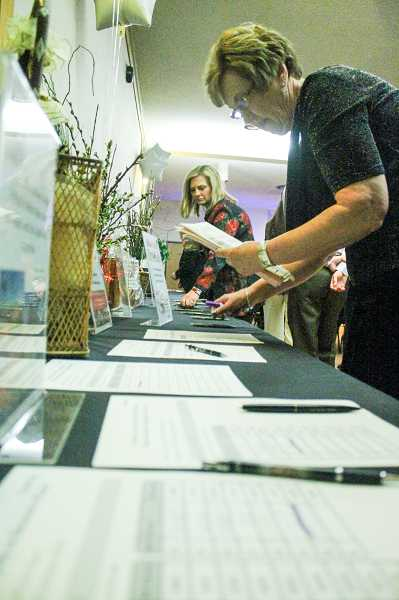 by: NEWS-TIMES PHOTOS: JOHN SCHRAG - Chamber board member Maggie Boehmer (left) of Summa Real Estate and former chamber director Lois Hornberger, now with Pacific University, collect bidding sheets from the first silent auction of the evening.