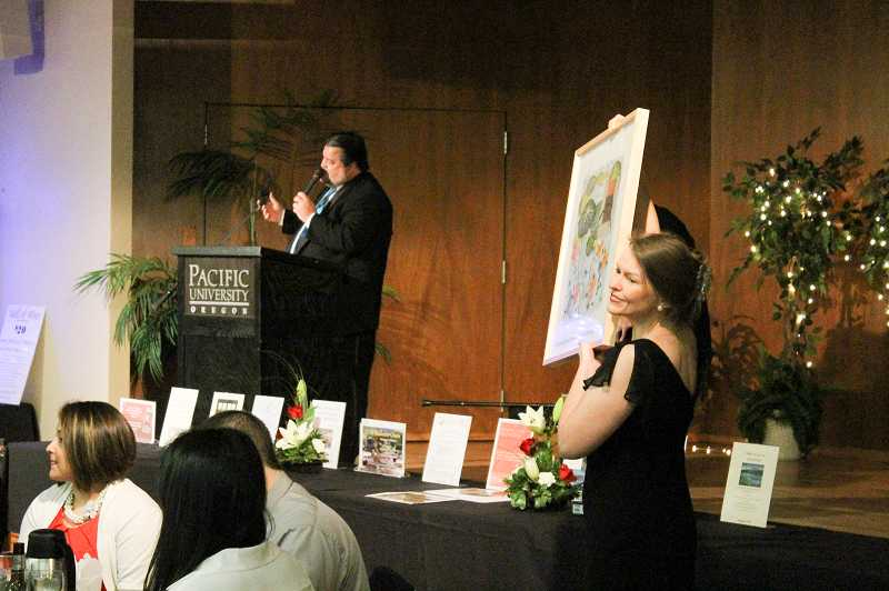 Forest Grove photographer Brenda Somes displays one of the three framed watercolor paintings by Mollie Favour (and donated by Viasystems) that went up for bid during oral auction.