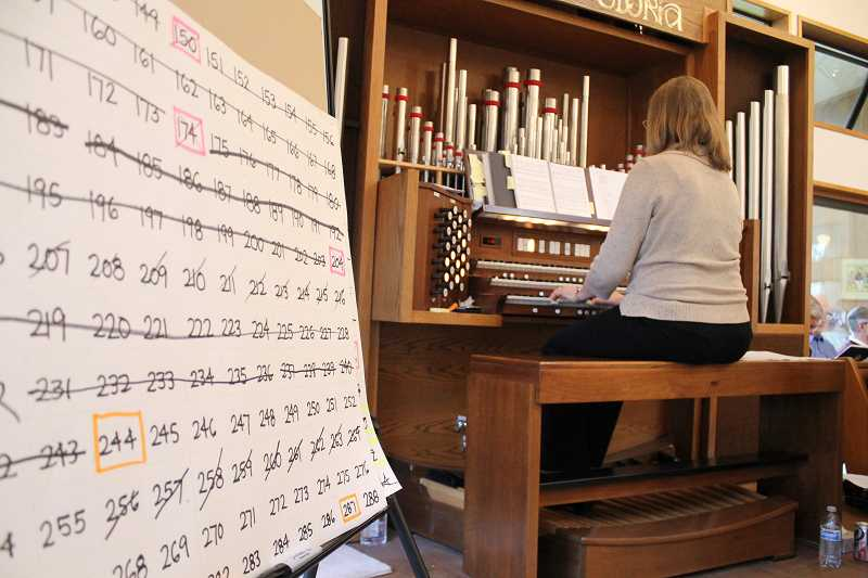 by: NEWS-TIMES PHOTO: JOHN SCHRAG - Hymn numbers are counted down Sunday on a white poster as organist Jeannine Jordan accompanies the St. Bedes Episcopal Church choir in Forest Grove.
