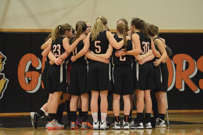 by: JOHN WILLIAM HOWARD - The Scappoose girls' basketball team takes a moment to themselves before tipping off against Gladstone in the program's first post-season game since 2007. First-year head coach David Spirlin has promised to return, and has plans to build on this year's foundation.
