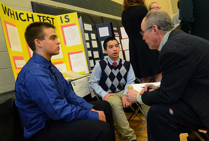 by: TIDINGS PHOTO: VERN UYETAKE - West Linn High freshmen Jeffery VanHorn, left, and Alec Garcia discuss their study of what kind of test works best with judge Randall Fastabend.