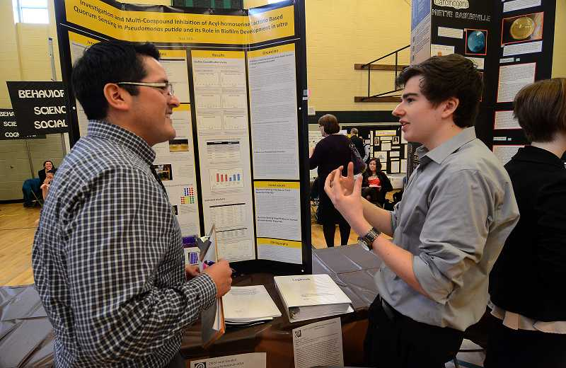 by: TIDINGS PHOTO: VERN UYETAKE - WLHS junior Nick Miller talks to judge David Valenzuela about his entry in the microbiology category.
