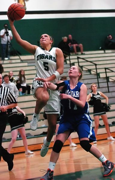by: DAN BROOD - SOARING -- Tigard High School senior guard Lexi Carter (left) goes up over McNary's Jasmine Ernest for two of her 23 points in Tuesday's playoff victory.