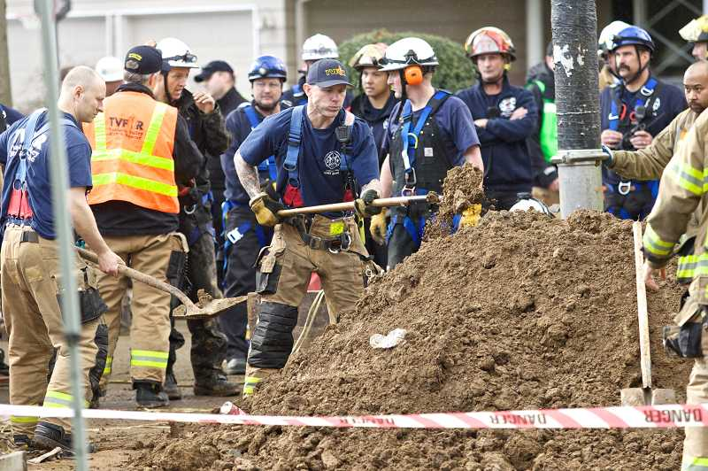 by: TIMES PHOTO: JAIME VALDEZ - Tualatin Valley Fire & Rescue firefighters excavate dirt to provide more room to help rescue a man trapped in a trench.