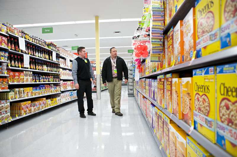 by: TIMES PHOTO: JAIME VALDEZ - Matt Cooper, an assistant manager at the Murray Boulevard Walmart Neighborhood Market, walks down the cereal aisle with the store manager, JD Fleming.