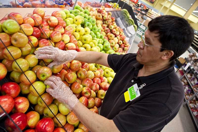 by: TIMES PHOTO: JAIME VALDEZ - Jose Fasado, a produce associate at the Sexton Mountain Walmart Neighborhood Market, arranges apples before the store's grand opening on Friday.