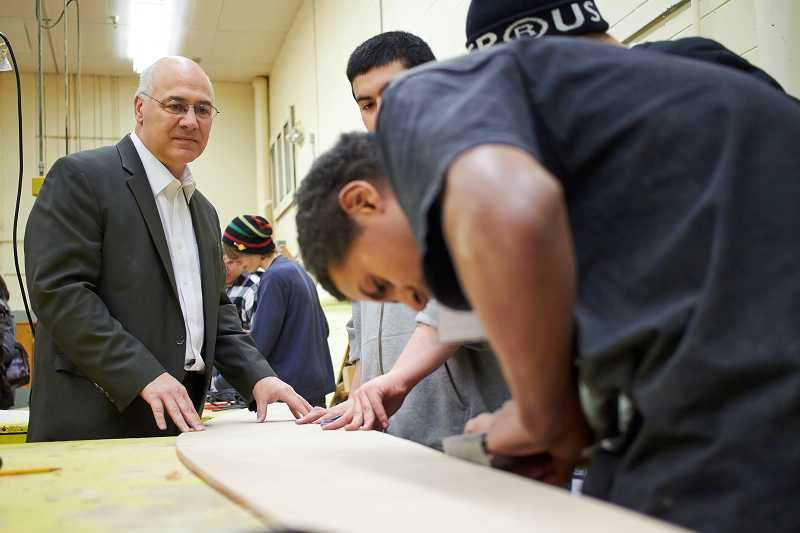 by: TIMES PHOTO: CHASE ALLGOOD - Oregon Labor Commissioner Brad Avakian holds a board as Merlo Station High School senior Micah Nichols planes the edges. Avakian visited the Wind and Oar wooden boat project at Aloha High School on Wednesday, Feb. 26.
