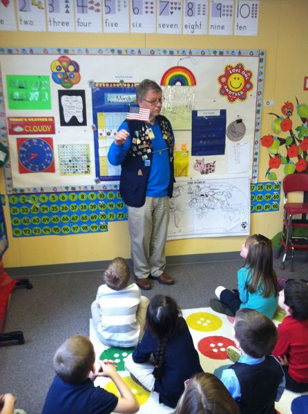 by: MARK MILLER - Hank Calhoun of the St. Helens Lions Club tells first-grade students at Columbia County Christian School about the importance of honoring the American flag Tuesday, March 4. Each student went home with his or her own small flag, which Calhoun advised the class to keep safe.