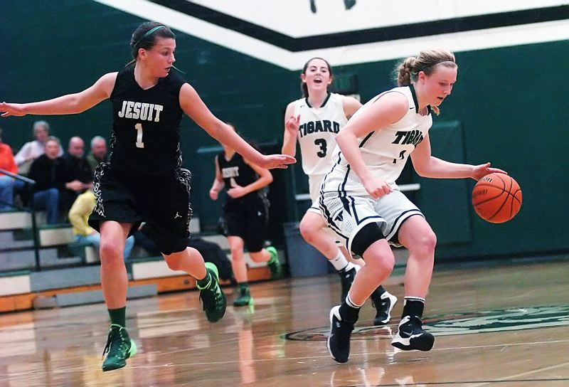 by: DAN BROOD - ON THE MOVE -- Tigard junior Kaylie Boschma (right) brings the ball up court against Jesuit sophomore Kate Andersen.