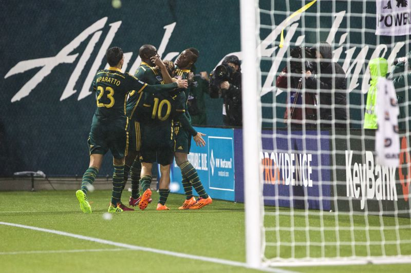 by: TRIBUNE PHOTO: JAIME VALDEZ - The Portland Timbers celebrate after Gaston Fernandez (10) strikes with the tying goal Saturday night in the final moments of a 1-1 season-opening draw with Philadelphia at Providence Park.