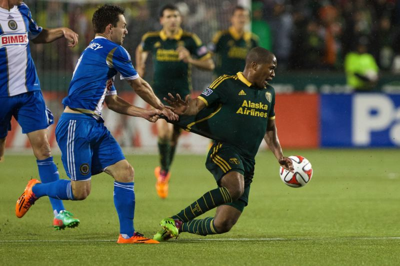 by: TRIBUNE PHOTO: JAIME VALDEZ - Union forward Jack McInerney (left) pulls Portland Timbers forward Frederic Piquionne's jersey in the second half.