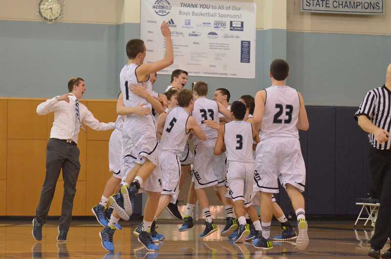 by: JEFF GOODMAN / PAMPLIN MEDIA GROUP - The Wilsonville boys basketball team celebrates its overtime win over Wilson in the first round of the Class 5A playoffs March 8. The Wildcats advanced to the state quarterfinals for the sixth year in a row.