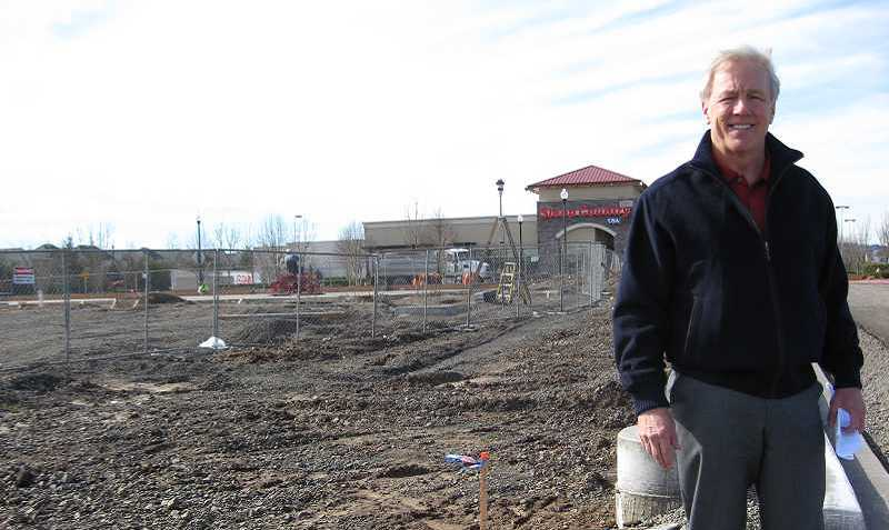 by: COURTESY OF GRAMOR DEVELOPMENT - Barry Cain, president of Gramor Development, stands in front of what will soon be Chipotle Mexican Grill. Plans are to begin opening the complex in August.