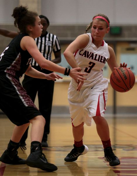 by: JON HOUSE - Kaitlyn Reiner fends off the defense as she brings the ball up the floor in the Cavaliers win over Tualatin. Reiner had a big night, scoring 21 points, assisting on her share of baskets and handling Tualatins defensive pressure.