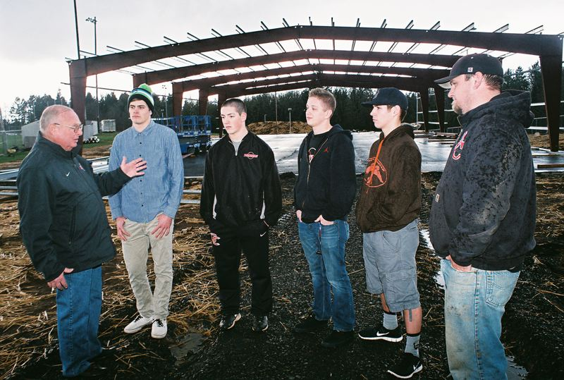 by: JOHN DENNY - Oregon City head baseball coach Greg Lord (left) and assistant coach Andy Chapin (right) meet with high school players (from left) Jack Powell, Clay Valenzuela-Reece, Jalen Satter and Terrel Hood to discuss the progress on the high schools new 80x160-foot baseball hitting facility (background).