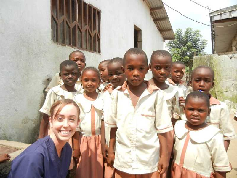 by: SUBMITTED PHOTO - Katy Sharman happily poses for a photo with her many children friends in Cameroon. She gave them all a head-to-toe checkup on their medical needs.