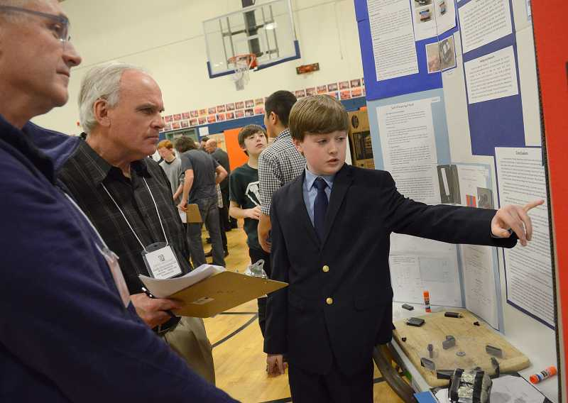 by: PAMPLIN MEDIA GROUP: VERN UYETAKE - Nathan Tidball discusses his science fair project with judges at the middle school science fair March 7.