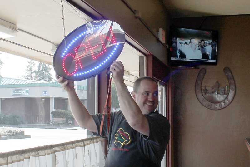 by: CORY MIMMS - Tim Bilyeu turns on the open sign for the first time at Passadore's Pizzeria.