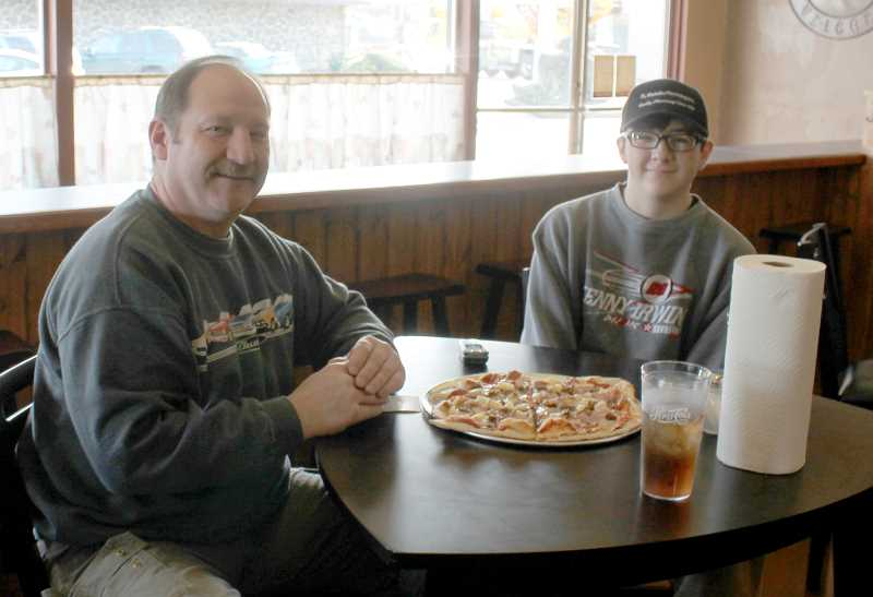 by: CORY MIMMS - John White and his 14-year-old son, Wyatt, were the first patrons of Passadore's Pizzeria, which opened last week.