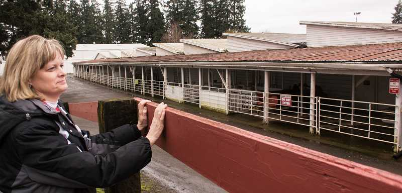 by: RAY HUGHEY - Laurie Bothwell, executive director of the Clackamas County Event Center, looks over the now-closed livestock barn.