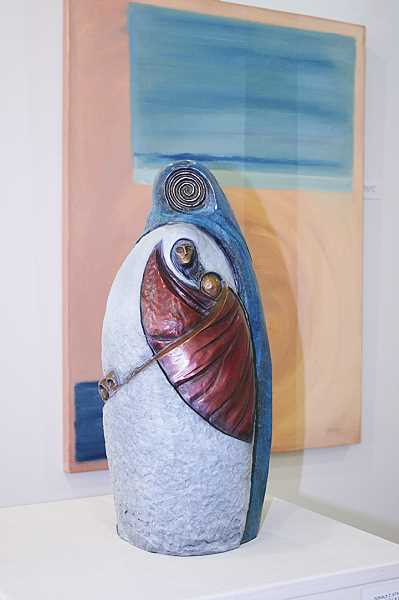 'Sacre Bleau: A Sacred Trust'  a bronze sculpture by Donald Stastny, stands in front of his painting 'Mother Earth.'