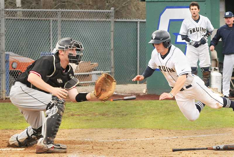 by: SETH GORDON - Airborne - Zac Israel dives to home plate to score the winning run in the 11th inning of George Fox's 1-0 victory over Pacific Sunday.