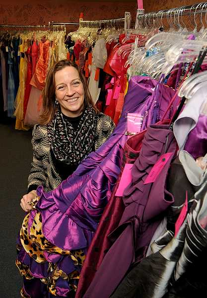 by: PAMPLIN MEDIA GROUP: VERN UYETAKE - Abby's Closet volunteer Lois Moll offers a preview of some of the gowns that will be given away at the nonprofits annual prom gown giveaway April 5 and 6.