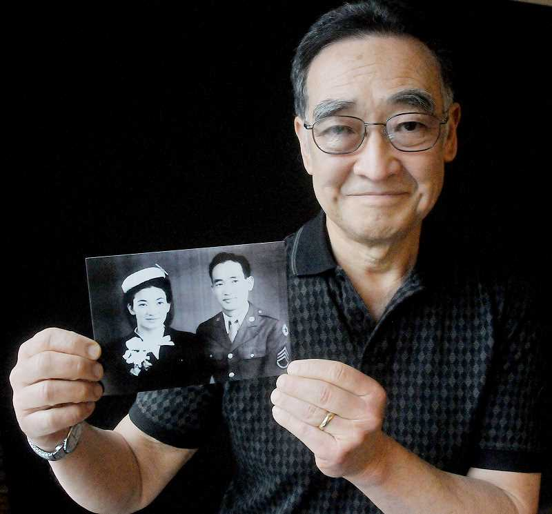 by: GARY ALLEN - History - Russell Yamada displays a photo of his parents, Kimi and Roy Yamada, taken while his father was home on leave from the war.