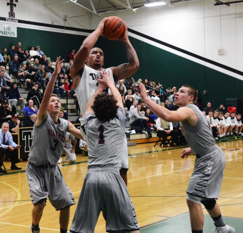 by: MATT SINGLEDECKER - TRIPLE TEAMED -- Tigard senior A.J. Hotchkins looks to go up to the basket between a trio of Westview defenders in last week's game.