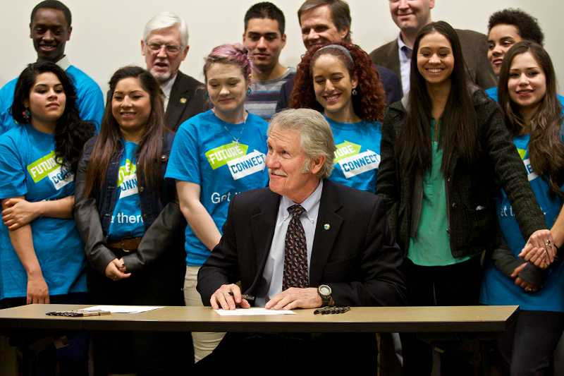 by: TIMES PHOTO: JAIME VALDEZ - Gov. John Kitzhaber smiles after signing House Bill 4116 as students in Portland Community College's Future Connect Program stand behind him at the Rock Creek campus on Tuesday.