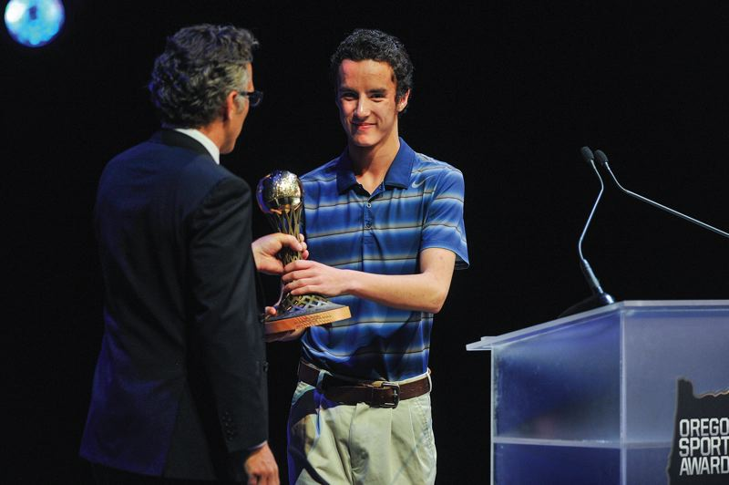 by: HILLSBORO TRIBUNE PHOTO: JOHN LARIVIERE - Century student Travis Koski receives an award for Special Olympics athlete of the year from Oregon Sports Awards host Neil Everett.