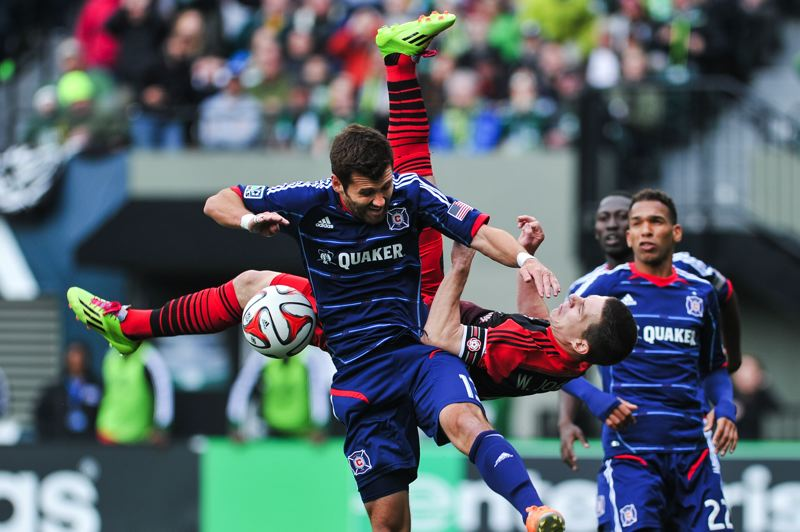 by: COURTESY OF JOHN LARIVIERE - Will Johnson of the Portland Timbers tries a bicycle kick in between Chicago Fire defenders.