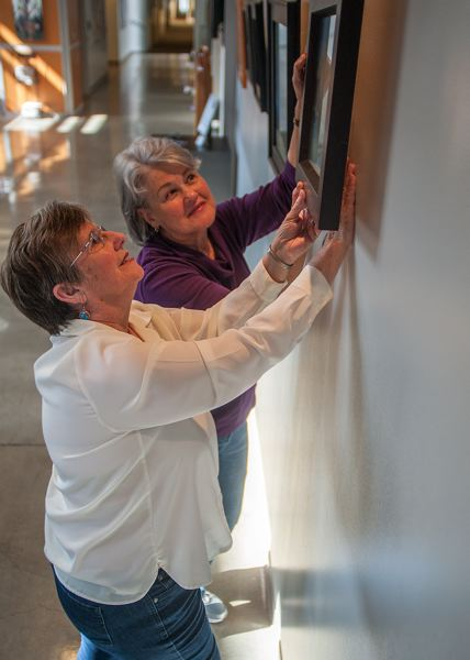 by: SPOKESMAN PHOTO: JOSH KULLA - Artists Irene Van Dusen, front, and Wendy Ware are shown hanging their work at the Clackamas Community College Wilsonville campus in preparation for the March 17 opening of Pastel Pleasures.