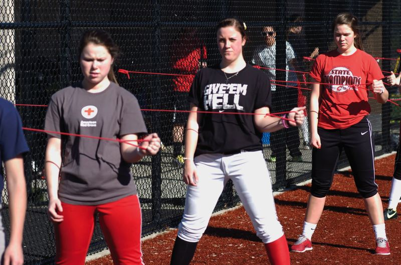 by: SANDY POST: PARKER LEE - Sandy pitcher Sammie Byron, middle, leads teammates through stretching drills during practice last week.