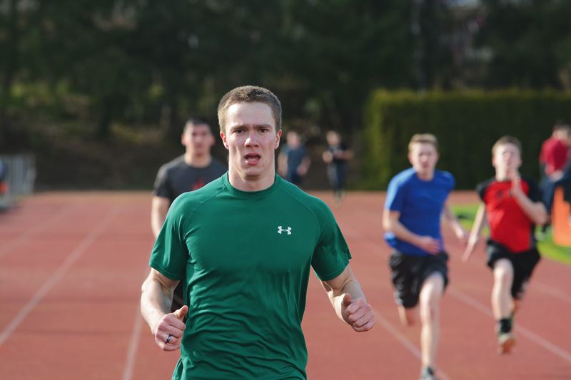 by: JOHN WILLIAM HOWARD - Scappoose's Keith Nickel leads a group of sprinters during timed trials at track practice on Monday, March 10. Head Coach David Harley has said the team's sprinters will be the core of the group, along with a number of distance standouts.