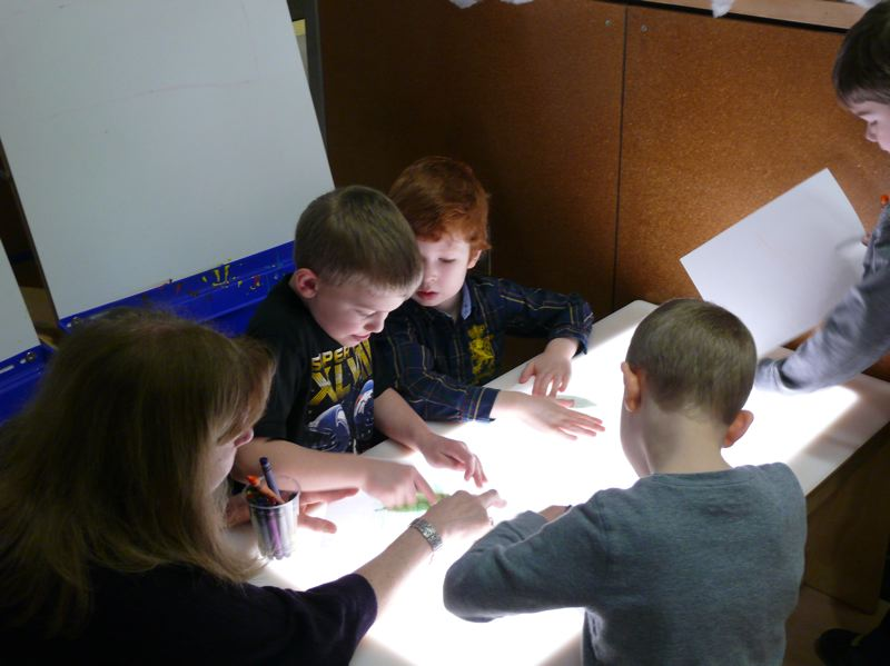 by: PHOTO COURTESY: LESLIE ROBINETTE - Students gather around a light table to make leaf rubbings in the Science Learning Zone at the Gladstone Center for Children and Families.