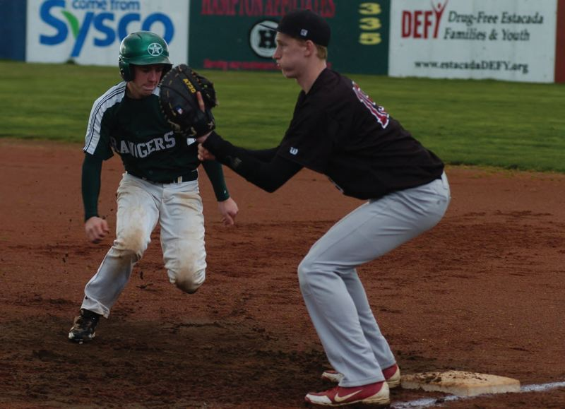 by: ESTACADA NEWS: PARKER LEE - Estacadas Kyle Beguelin scampers back to first base safely during Mondays extra-inning draw with Sandy.