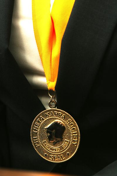 by: OUTLOOK PHOTO: JIM CLARK - Whitlock dons her Phi Theta Kappa medal. She serves as president of the MHCC honors society.