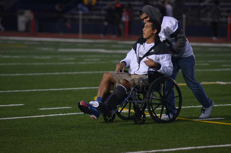 by: JEFF GOODMAN / FILE - Canby junior Devon Fortier pushes senior teammate Sam Bodines wheelchair this past football season before a road game against Lake Oswego. Fortier, who had a breakout sophomore season, missed the entire year after blowing out his knee at a football showcase over the summer. Bodine sustained season-ending injuries in the Cougars conference opener against Oregon City.