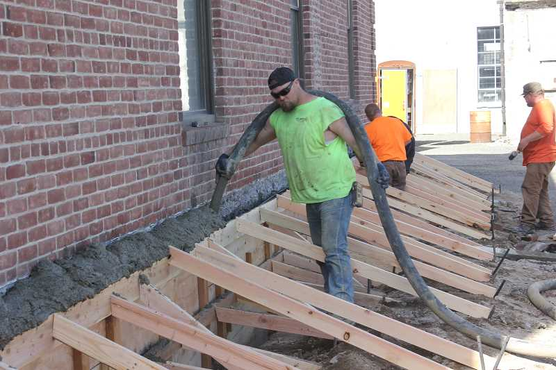 by: SUSAN MATHENY/MADRAS PIONEER - Workers pour cement into wooden frames for the foundation.