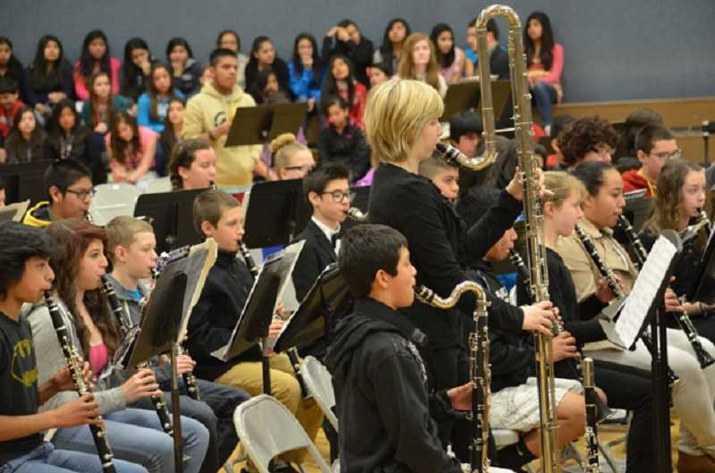 by: JANIS BRENTANO - A mixed group of Woodburn band students and the Portland Youth Woodwind Ensemble performs at Valor Middle School Wednesday. The ensemble featured both common and unusual instruments, including the 6-foot contrabass clarinet (above, center).