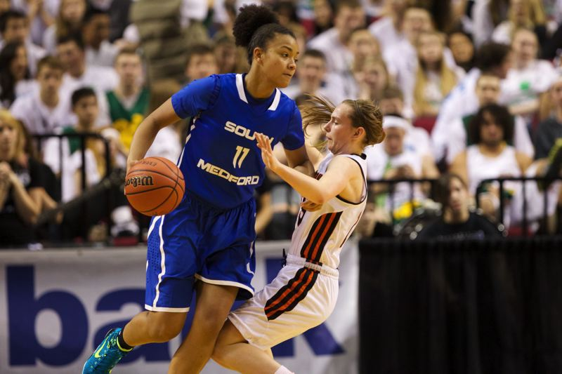 by: TIMES PHOTO: JAIME VALDEZ - South Medford Panthers guard Ashley Bolston powers through Beaverton Beavers guard Allison Mueller in the second half of the 6A girls semifinals at Moda Center.