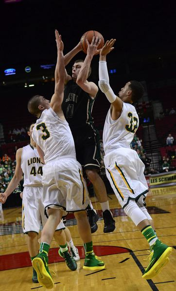 by: TIMES PHOTO: VERN UTEYKE - Jesuit senior shooting guard Dan Nelson goes up over West Linn's Payton Pritchard and Anthony Mathis in the paint.