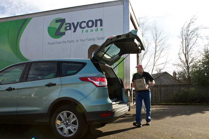 by: TIMES PHOTO: JAIME VALDEZ - Dale McLaughlin, fleet manager at Zaycon Foods, loads groceries into a vehicle at Tigard Community Friends Church. The grocery store makes deliveries in Tigard for folks to pick up pre-ordered groceries like chicken, pork and fruits.