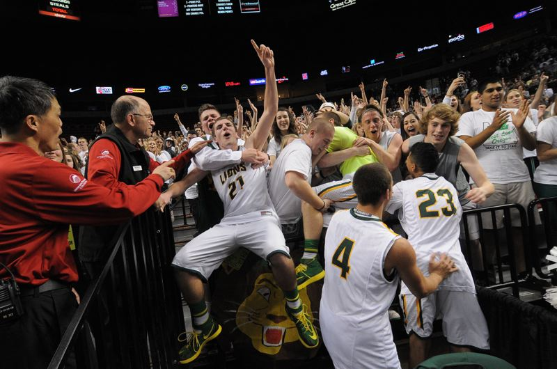 by: VERN UYETAKE - Kevin Edwards and other members of the West LInn boys basketball team jump into the arms of the student section after the Lions captured their second state title in a row.