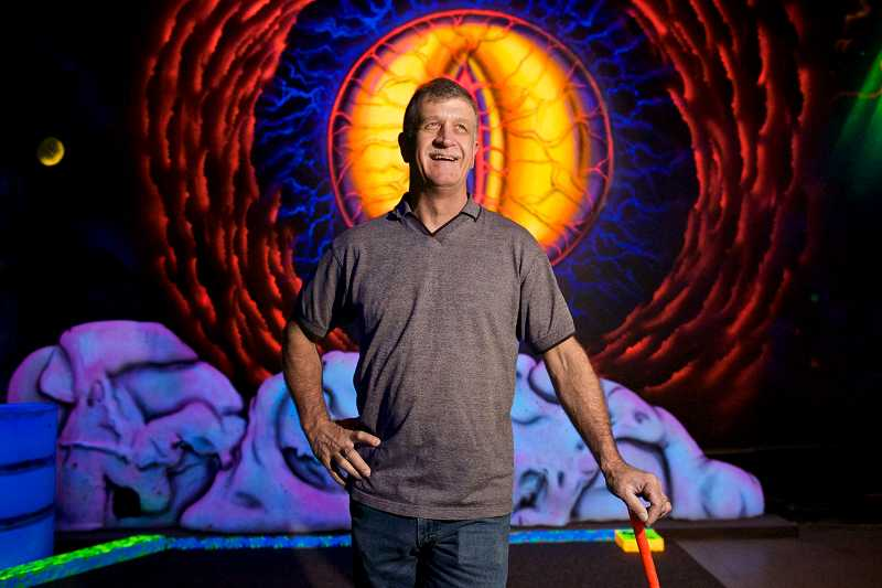 by: TIMES PHOTO: JAIME VALDEZ - Ray Latocki, owner of 13th Door Haunted House, stands in front of an eye painted on a wall at his remodeled business, Glowing Greens, an indoor black-light miniature golf course.
